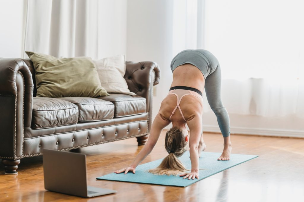 Person doing yoga with laptop